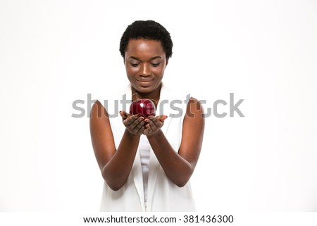 Attractive cheerful african american young woman holding big red apple on palms over white background - stock photo