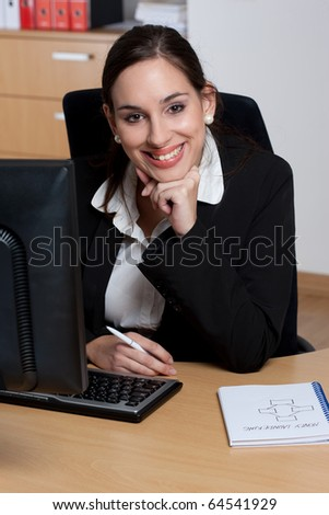 Attractive cheerful and positive young businesswoman in her office