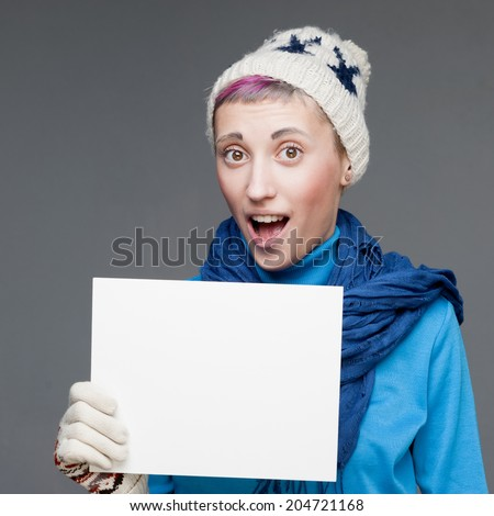 attractive cheerful caucasian young woman in winter clothing holding sign over gray background - stock photo