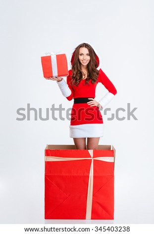 Attractive cheerful curly young lady in red santa claus costume with hood jumping out of present box holding red gift box over white background - stock photo