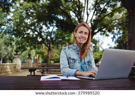 Attractive cheerful female student thinking about something good while sitting with portable net-book in University park, smiling woman enjoying good day while preparing coursework on laptop computer - stock photo