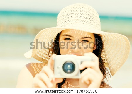 Attractive cheerful summer woman talking pictures with digital camera . - stock photo