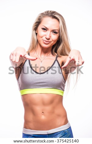 Attractive cheerful young female athlete  pointing on you over white background - stock photo