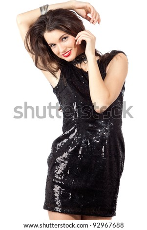 Attractive cheerful young woman posing in sequin dress, looking at camera. Studio image, isolated on white background. - stock photo