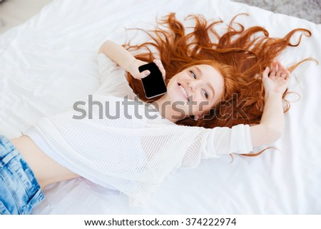 Attractive cheerful young woman with long red hair lying and holding blank screen mobile phone - stock photo