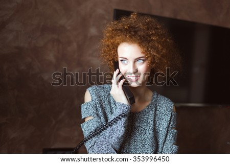 Attractive cheerful young woman with red curly hair talking on telephone at home  - stock photo
