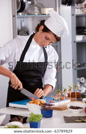 Attractive chef cutting an onion - stock photo
