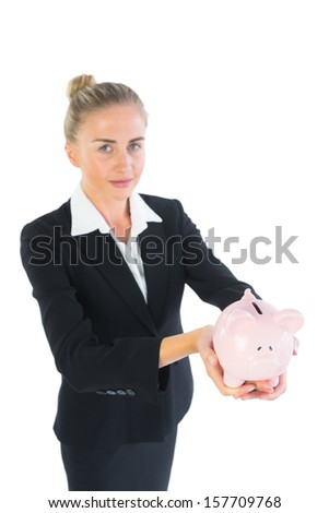 Attractive chic businesswoman presenting a piggy bank looking at camera