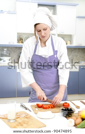 Attractive chief cook preparing food , cutting tomatoes