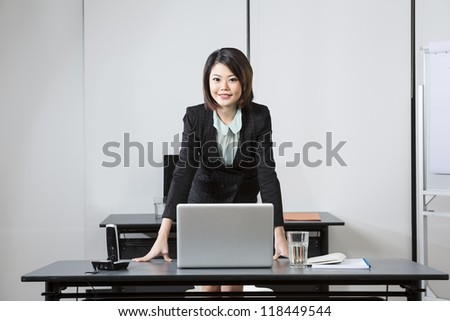 Attractive Chinese Business Woman leaning on her desk. - stock photo
