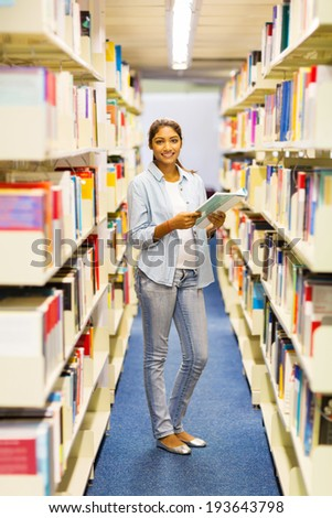 attractive college girl reading in library - stock photo