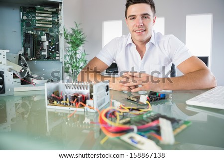 Attractive computer engineer sitting at desk smiling at camera in bright office - stock photo