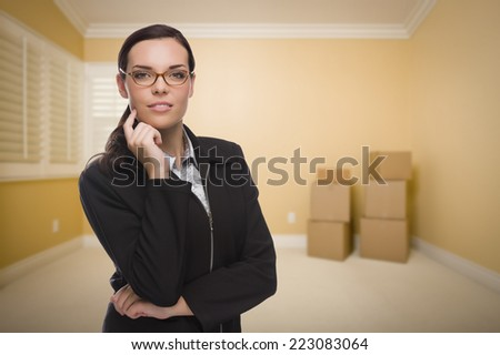 Attractive Confident Mixed Race Woman in Empty Room with Boxes. - stock photo