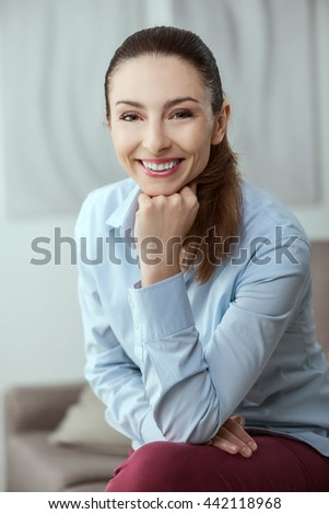 Attractive confident woman sitting on a couch, she is smiling at camera and posing - stock photo