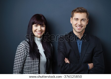 Attractive confident young business partners posing together with folded arms in front of a dark studio background smiling at the camera, man and woman - stock photo