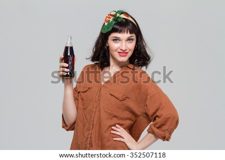 Attractive confident young woman posing with  bottle of sweet carbonated beverage isolated over grey background - stock photo