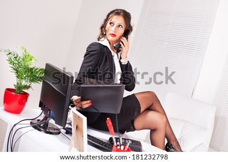 Attractive coquettish secretary sitting on desk and talking on the phone