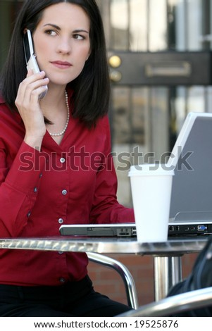 Attractive corporate, business woman working on her laptop outdoors, on cell phone and enjoying a cup of tea, city environment - stock photo