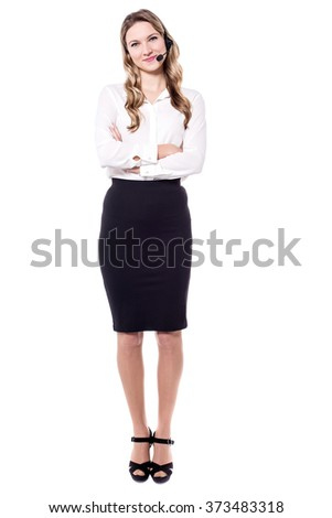 Attractive corporate executive standing with crossed arms - stock photo