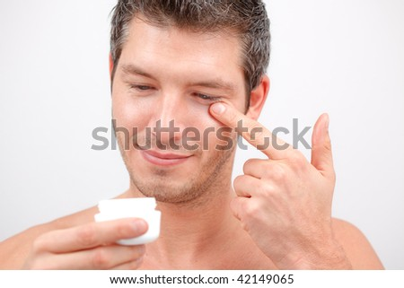 Attractive cosemetic man with wide open eyes making fun smiling - stock photo