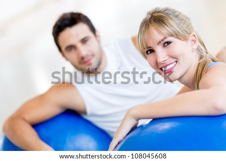 Attractive couple at the gym exercising with Pilates balls - stock photo