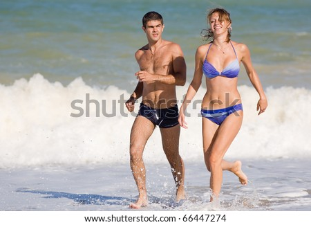 Attractive couple at the sea. Young man and young woman on the beach during the surf