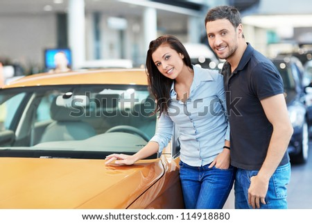 Attractive couple chooses a car - stock photo