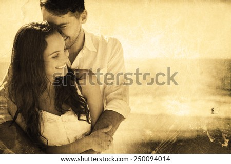 Attractive couple cuddling against grey background - stock photo