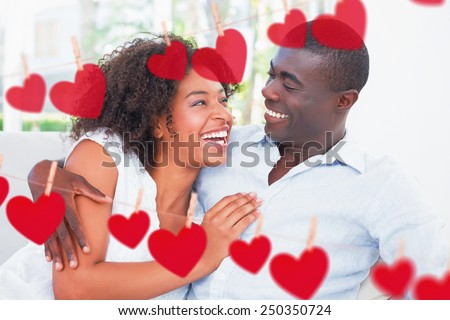 Attractive couple cuddling on the couch against hearts hanging on a line - stock photo