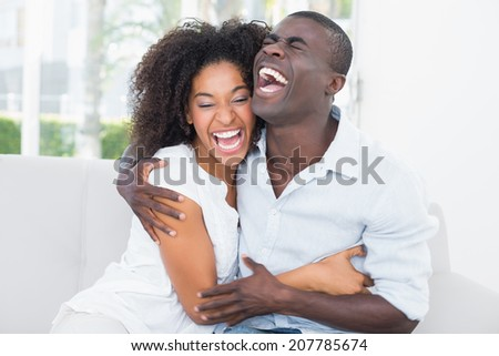 Attractive couple cuddling on the couch at home in the living room - stock photo