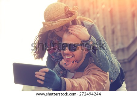 Attractive couple doing selfie outdoors. - stock photo
