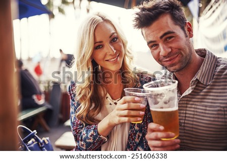 attractive couple drinking beer at outdoor restaurant - stock photo