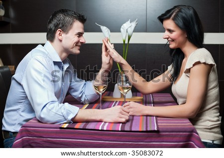Attractive couple drinking wine and flirting - stock photo