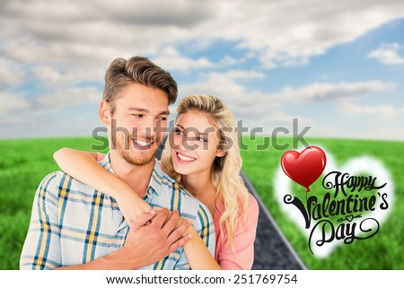 Attractive couple embracing and smiling against road on grass - stock photo