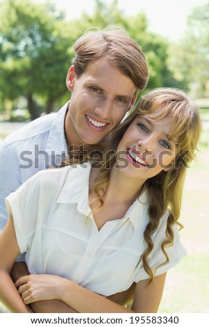 Attractive couple embracing and smiling at camera in park on a sunny day