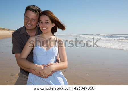 Attractive couple embracing on the beach on a sunny day