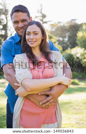 Attractive couple embracing smiling at camera in a park