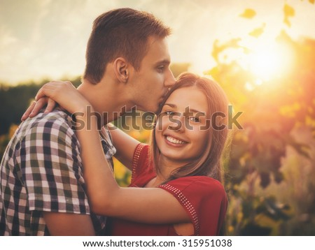 Attractive couple enjoying romantic date in the Countryside, sunset in the background / Vintage style photo with custom white balance, color filters, and some fine film grain added - stock photo