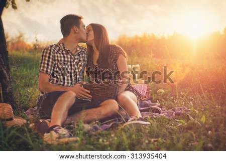 Attractive Couple Enjoying Romantic Sunset Picnic in the Countryside / Vintage style photo with custom white balance, color filters, and some fine film grain added - stock photo