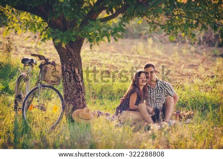 Attractive Couple Enjoying Romantic Sunset Picnic in the Countryside / Vintage style photo with custom white balance, color filters, soft focus effect, and some fine film grain added - stock photo