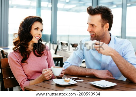 Attractive couple having a conversation  in a canteen - stock photo