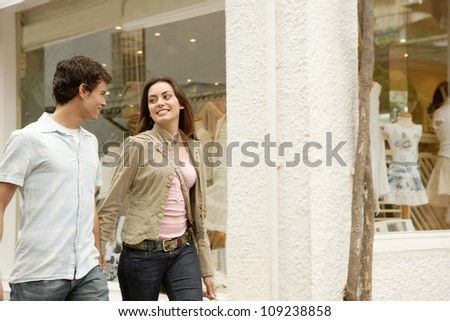 Attractive couple having breakfast in an exotic garden while on vacations, smiling. - stock photo