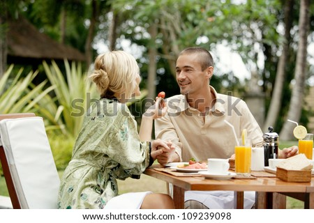 Attractive couple having breakfast in an exotic garden while on vacations, smiling.
