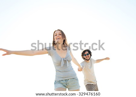 Attractive couple holding hands and being playful in a beach destination, joyfully smiling and being dynamic against a sunny sky, holiday in the sun outdoors. Travel and healthy living lifestyle. - stock photo
