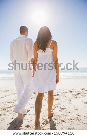 Attractive couple holding hands and walking to the water at the beach