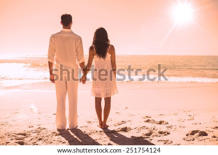 Attractive couple holding hands and watching the waves at the beach - stock photo