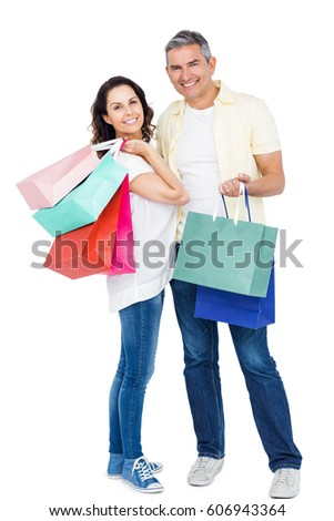 Attractive couple holding shopping bags against white background