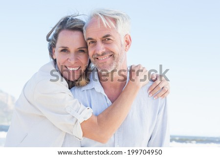Attractive couple hugging at the beach smiling at camera on a sunny day - stock photo