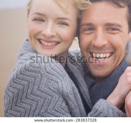 Attractive couple hugging on the beach in warm clothing - stock photo