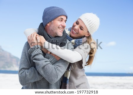 Attractive couple hugging on the beach in warm clothing on a bright but cool day - stock photo